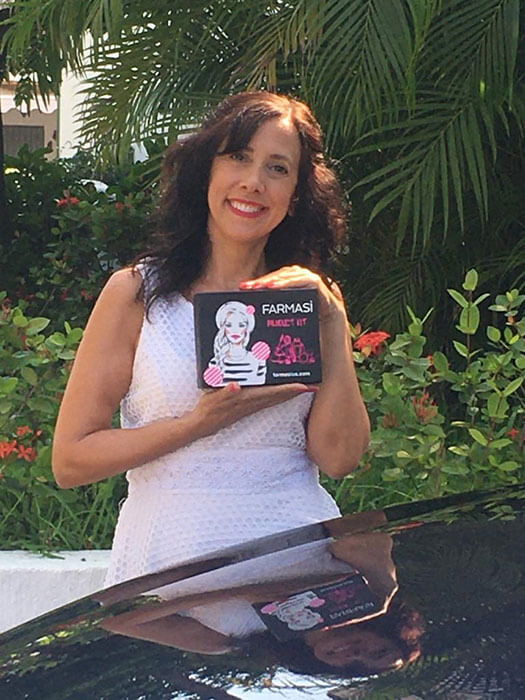 Suzanne Sanford, the CEO of Elevatest, holding up a Farmasi beauty product